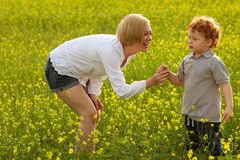 Mother and Son Having Fun. Mom giving flower to her son. outdoor shot Stock Image