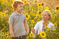 Mother and Son Having Fun. In the field of sunflowers. Mother giving sunflower to her son. outdoor shot Royalty Free Stock Photo