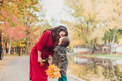 Mother and son having fun in the autumn park among the falling leaves. Autumn concept. stock photo