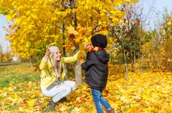 Mother and son having fun in the autumn park among the falling leaves. royalty free stock photo