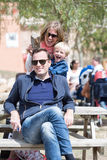 Mother and son having fun behind father. Family outdoor in summer having fun while sitting on bench stock photos