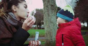 Mother and son having fun with bubbles in park. Happy family. stock video