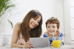 Mother and son having fun with a digital tablet in home Royalty Free Stock Photo