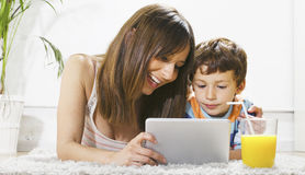 Mother and son having fun with a digital tablet in home Stock Image