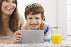 Mother and son having fun with a digital tablet in home Royalty Free Stock Photos