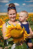 Mother and son having fun in the field of sunflowers. Outdoor Royalty Free Stock Photography