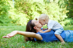 Mother and son having fun on the grass in park Stock Images