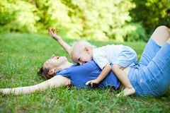 Mother and son having fun on the grass in park Royalty Free Stock Photos