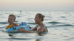 Mother and son having fun playing in the sea. Mother and little son enjoying playing in the sea. Woman spinning excited boy in rubber ring. Family fun during stock video footage