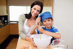 Mother and son having fun preparing dough Stock Photos