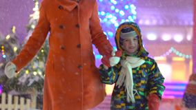 Mother and son having fun and run holding hands on the background of Christmas street. Christmas tree. Attractive family stock video
