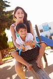 Mother And Son Having Fun On Seesaw In Playground stock photography