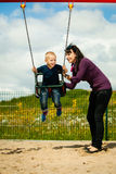 Mother and son having fun on a swing outside. Mother and her little son having fun together at the playground. Child kid playing on a swing. Happy healthy stock photos