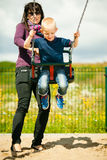 Mother and son having fun on a swing outside. Mother and her little son having fun together at the playground. Child kid playing on a swing. Happy healthy stock photo