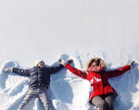 Mother and son having fun together lounging in the snow. On a sunny winter day, copy space royalty free stock image