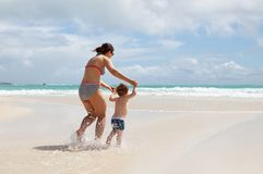 Mother and son having fun on a tropical beach Stock Image