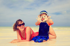 Mother and son having fun with water at beach Stock Image