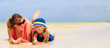 Mother and son having fun with water at beach Royalty Free Stock Photos