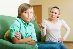 Mother and son having quarrel. Mature mother and teenager son having conflict in home interior Stock Photography