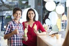 Mother And Son Having Vanilla Ice Creams At Counter Stock Photo