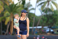 Mother and son on a Hawaiian black sand beach. Portrait of a young mother holding her little son on a Hawaiian black sand beach Stock Images