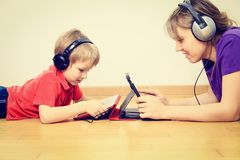 Mother and son with headset looking at touch pad Stock Photos