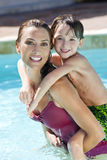 Mother With Son On Her Shoulders In Swimming Pool. A beautiful mother having fun with her son on her shoulders in a swimming pool stock photography