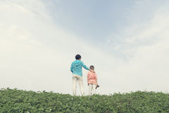 Mother son on hillside together. Chinese mother son standing on hillside together, mothers hand on sons shoulder ,  looking far away Stock Photos