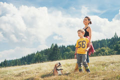 Mother with son and his dog walk on the golden field Royalty Free Stock Photo