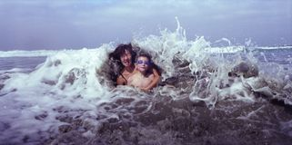 Mother and Son Hit by Wave Stock Photography
