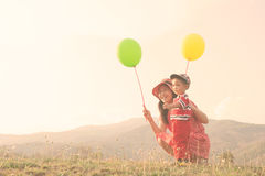 Mother and son hold ballon and playing outdoors at sunset Stock Photos