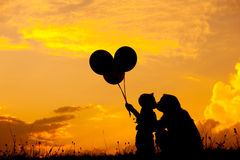Mother and son hold balloon and playing outdoors at sunset silhouette Stock Images