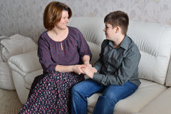 Mother and son hold hands and look at each other Stock Photo