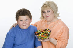 Mother And Son Holding Bowl Of Salad. Portrait of mother and son holding bowl of salad isolated over white background royalty free stock photography