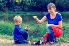 Mother and son holding fish they caught. On the lake Royalty Free Stock Photography
