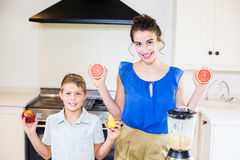Mother and son holding fruits in kitchen Royalty Free Stock Photo