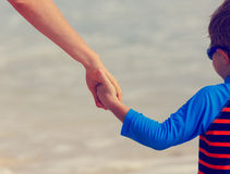 Mother and son holding hands on the beach Stock Images