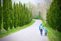Mother and son holding hands run through a driveway lined with cypresses backpacking along a journey together for life Stock Image