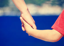 Mother and son holding hands at sea. Mother and son holding hands on sea vacation, family travel stock photos