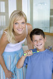 Mother and son (6-8) holding toothbrushes in bathroom, smiling, portrait Stock Image