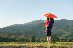 A mother and son holding umbrella and playing outdoors at sunset Royalty Free Stock Image