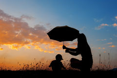 A mother and son holding umbrella and playing outdoors at sunset Stock Images
