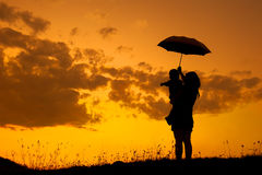 A mother and son holding umbrella and playing outdoors at sunset Royalty Free Stock Photos