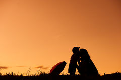 A mother and son holding umbrella and playing outdoors at sunset. Silhouette royalty free stock photography