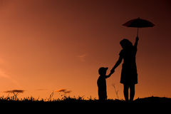 A mother and son holding umbrella and playing outdoors at sunset Stock Photos