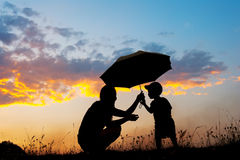 A mother and son holding umbrella and playing outdoors at sunset Royalty Free Stock Photo