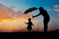 A mother and son holding umbrella and playing outdoors at sunset Stock Photography