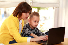 Mother and son at home doing lesson looking at laptop Stock Photography