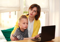 Mother and son at home doing lesson looking at laptop Stock Image