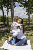 Mother and son hugging on the field. Emotioned mother hugging her son on the field sitting in the floor Royalty Free Stock Images